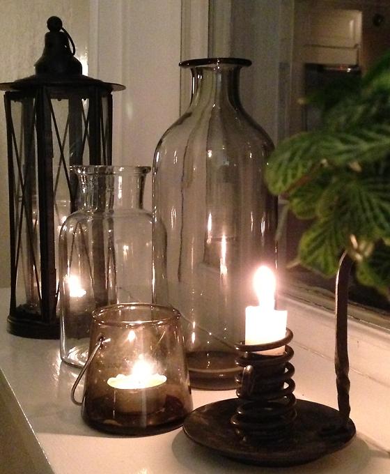 Ljuslyktor och glasvaser på fönsterbräda